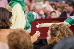 Holy Week in Malaga, Spain. Girl receiving candle wax. Royalty Free Stock Image