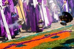 Holy Week procession, Antigua, Guatemala. ANTIGUA, GUATEMALA - APRIL 10, 2009: Purple clad cucuruchos carrying incense burners walking over a carpet or alfombra Stock Photos