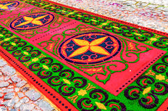 Holy Week processional carpet, Antigua, Guatemala. Antigua, Guatemala - March 1, 2015: Handmade carpet (alfombra) made of dyed sawdust in path of Holy Week stock photography