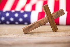 Holy Christian Cross and American Flag Background. A holy wooden Christian cross laying on a wood background with an American flag royalty free stock photography
