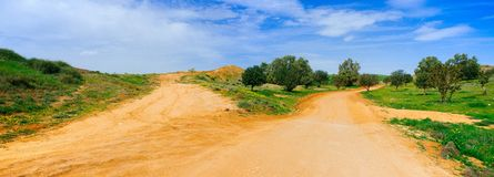 Holyland Series - Desert Road Panorama. A Panoramic view of yellow dirt road in in the Northern Negev Desert with dramatic sky in the background Royalty Free Stock Photography