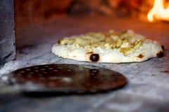Holz abgefeuerte Pizza, die gedreht wird lizenzfreie stockfotografie