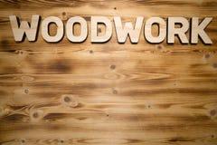 HOLZARBEIT-Wort gemacht mit Bausteinen auf hölzernem Brett lizenzfreie stockfotografie