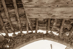Holzbalken und Steinbogen aufgegebenen Gebäude Sepia getont stockbild