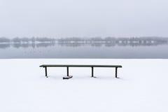 Holzbank auf der schneebedeckten Küste des Sees Lizenzfreies Stockbild