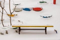 Holzbank auf einer schneebedeckten Straße lizenzfreie stockbilder