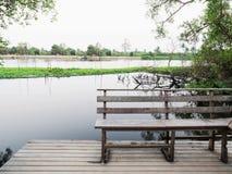 Holzbank auf Flussufer mit ländlicher Szene Lizenzfreie Stockfotografie