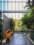 Holzbank auf Terrasse im Freien mit grünen Bäumen im Glaskamin für Hintergrund lizenzfreie stockfotos