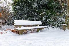 Holzbank bedeckt im frischen Schnee Stockfoto