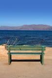 Holzbank, die das Meer übersieht Lizenzfreie Stockfotografie