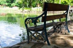 Holzbank, die einen Teich übersieht Lizenzfreie Stockbilder