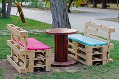 Holzbank gemacht von den Paletten für das Sitzen mit der Tabelle gemacht von der Spule der elektrischen Leitung Lizenzfreie Stockfotos