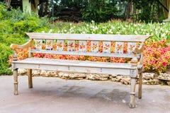 Holzbank im schönen Gartenhintergrund Lizenzfreies Stockfoto