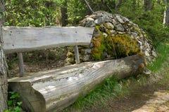 Holzbank und ein Steinbrunnen Stockfotografie