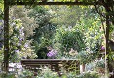 Holzbank unter hölzerner Überdachung, mit Ansicht auf wohlerhaltenen, gut gefüllt abgelegenen Garten lizenzfreie stockbilder