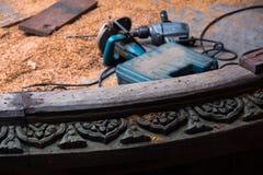 Holzbearbeitungswerkzeuge und -Holzspäne hinter geschnitzter hölzerner Skulptur am Schongebiet der Wahrheit in Pattaya, Thailand Lizenzfreies Stockfoto
