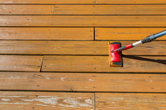 Holzbeize mit einer Farbenauflage auf hölzernem Patioboden Lizenzfreie Stockbilder