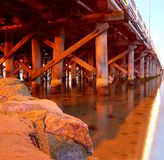 Holzbock der Pierbrücke über Fluss und Felsen Stockfotografie