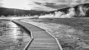 Holzbrücke über dampfigem Gelände in Yellowstone bei Sonnenuntergang Lizenzfreie Stockbilder