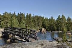 Holzbrücke über einem kleinen Fluss mit einem Wald im Hintergrund Lizenzfreie Stockfotografie