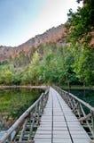 Holzbrücke über einem See in den Bergen Lizenzfreie Stockfotografie