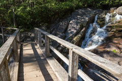 Holzbrücke über laufendem Fluss auf einem Wanderweg Stockfoto