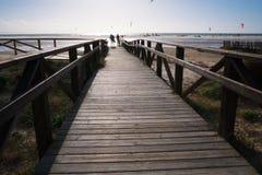 Holzbrücke auf Strand mit dunklen Wolken vor Sturm in Tarifa, Spanien stockfotografie