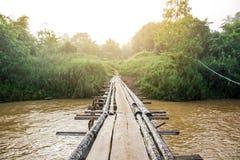 Holzbrücke, die den Fluss kreuzt Lizenzfreies Stockfoto