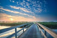 Holzbrücke durch den Fluss bei Sonnenaufgang Stockfoto