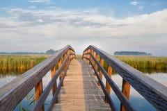 Holzbrücke durch Fluss Stockbild