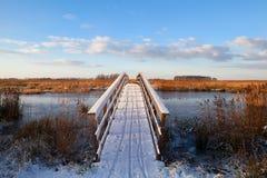 Holzbrücke durch Fluss im Schnee Stockbilder