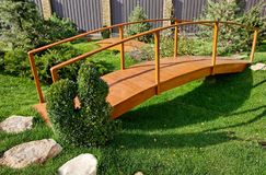 Holzbrücke in einem schönen Garten mit grünem Gras und evergre Lizenzfreie Stockfotografie