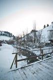 Holzbrücke in einem traditionellen rumänischen Dorf über einem kleinen Fluss Brücke über gefrorenem Fluss Winterlandschaftslandsc Lizenzfreie Stockfotos