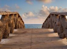 Holzbrücke hergestellt von den Palmenstämmen, die zu die Seeküste mit teils bewölktem Himmel in der Sonnenaufgangzeit am allgemei Stockbilder