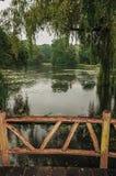 Holzbrücke unter Gärten mit Bäumen an einem regnerischen Tag an De Haar Castle, nahe Utrecht Lizenzfreie Stockfotografie
