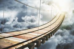 Holzbrücke in den Wolken, die zum Sonnenlicht gehen Lizenzfreies Stockfoto