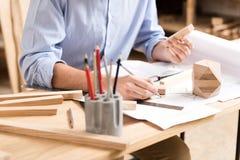 Holzen Sie den Handwerker ab, der Entwürfe von zukünftigen Produkten am Arbeitsplatz herstellt Lizenzfreie Stockfotografie