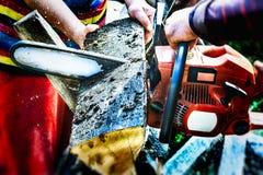 Holzfäller, der eine Kettensäge verwendet, um Brennholz zu machen Stockfotografie