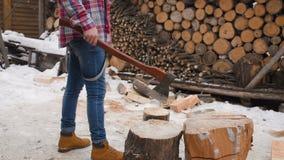 Holzfäller, der Holz mit einer Axt im Schnee hackt stock video footage