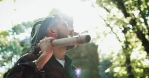 Holzfäller, der im Wald mit seiner Axt, herum schauend steht Porträt des hübschen bärtigen Mannes mit Axt stock footage