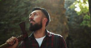 Holzfäller, der im Wald mit seiner Axt, herum schauend steht Porträt des hübschen bärtigen Mannes mit Axt stock video footage