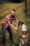 Holzfäller im Hemd, das firewoods hackt, Chips fliegen auseinander stockfotografie