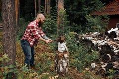 Holzfäller im Hemd, das firewoods hackt, Chips fliegen auseinander lizenzfreies stockbild