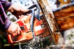 Holzfäller mit einer Kettensäge, die Brennholz macht Stockbilder