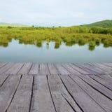Holzfußboden-Perspektive mit Landschaftswaldhintergrund stockbilder