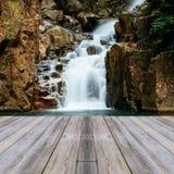 Holzfußbodenperspektive und natürlicher Wasserfall stockfotografie