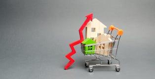 Holzhäuser in einem Einkaufswagen und in einem roten Pfeil oben Das Konzept der Erh?hung der Kosten der Wohnung Hohe Nachfrage f? lizenzfreie stockfotos