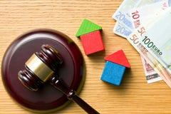 Holzhäuser mit Geld- und Richterhammer Stockfotografie