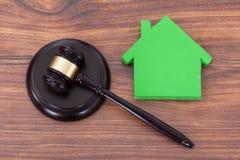 Holzhammer auf Block durch Modell des grünen Hauses Lizenzfreie Stockfotos