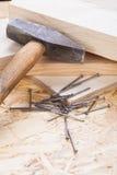 Holzhammer mit Nägeln und Planken des neuen Holzes Stockfotografie